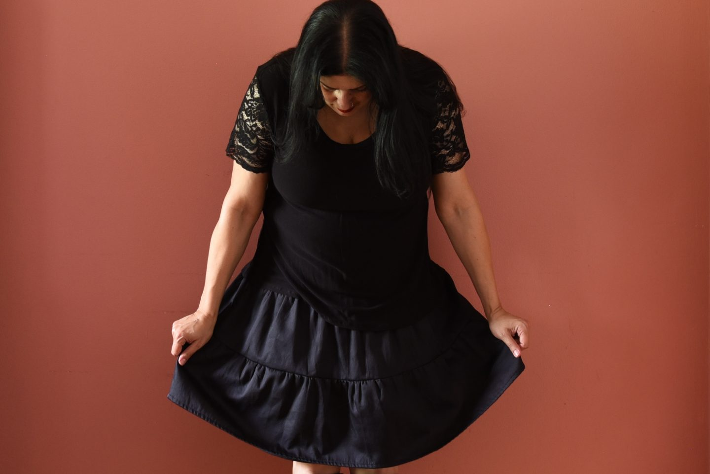Image of a woman with long black hair looking down wearing a black top with lace sleeves, a black skirt with gathered panels, knee-high black books standing in front of a pink wall.