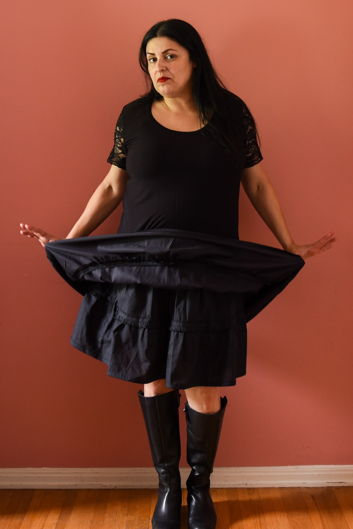 Image of a woman with long black hair wearing a black top with lace sleeves, a black skirt with gathered panels, knee-high black books standing in front of a pink wall holding the skirt up to expose the lining of the skirt.