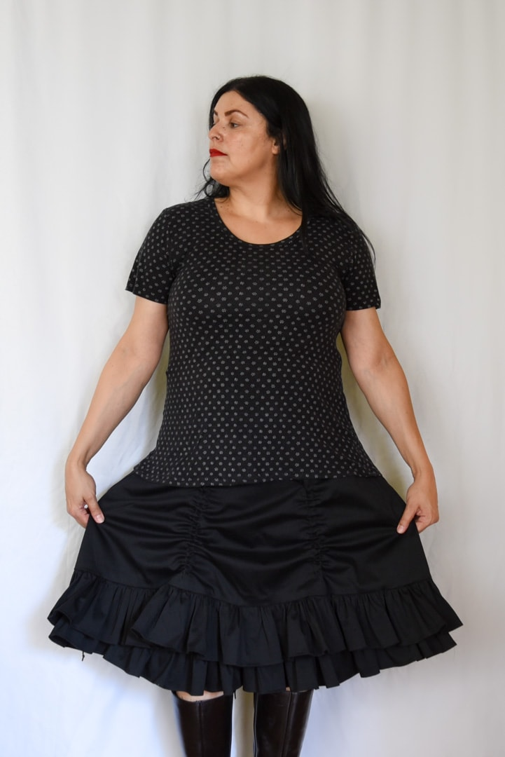 Image of woman with long black hair wearing a polka-dotted T-shirt and a Victorian-inspired black skirt with two layers with the top layered raised by two channels in front