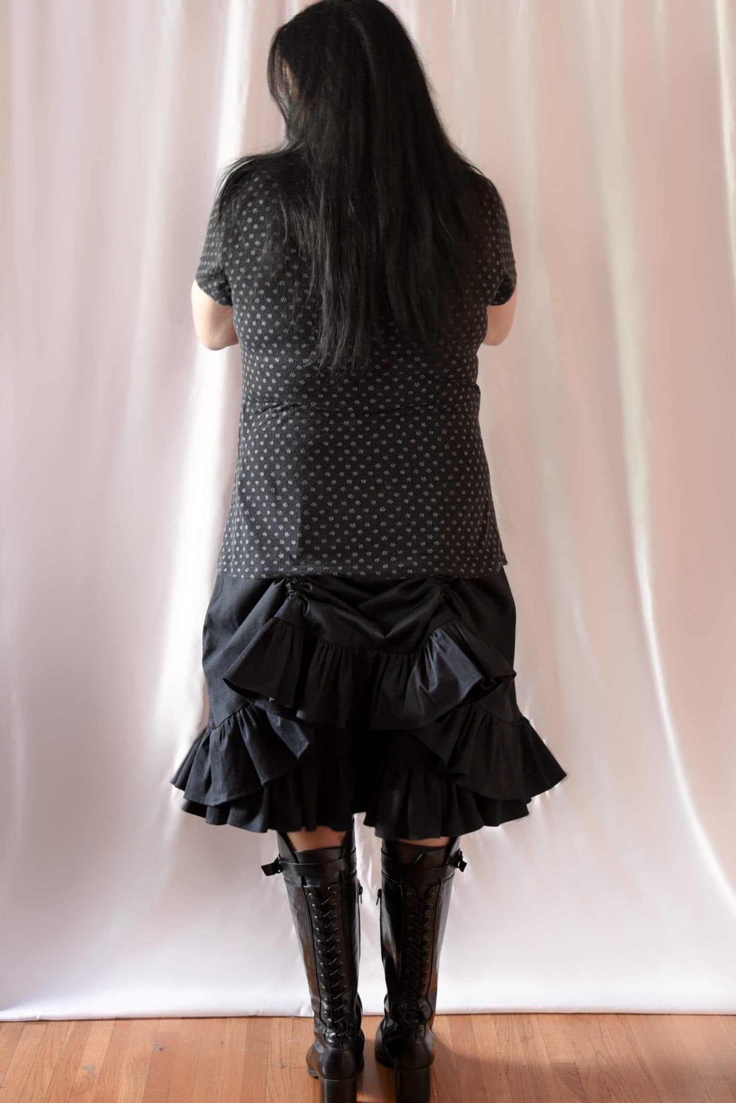 Image of woman back to the camera with long black hair wearing a polka-dotted T-shirt and a Victorian-inspired black skirt with with two layers with the top skirt with two channels raised to created a bustle effect