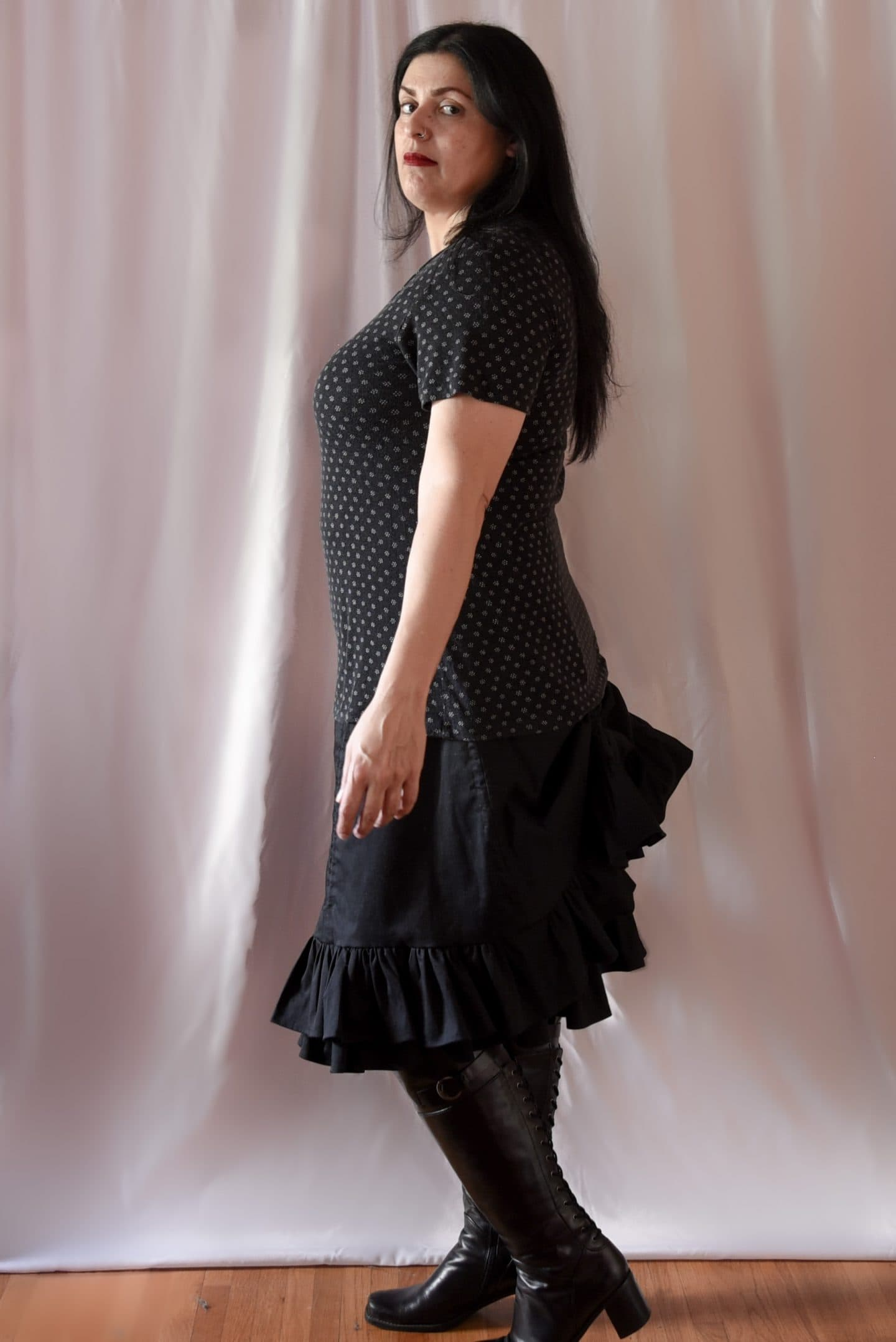 Image of woman sideways to the camera with long black hair wearing a polka-dotted T-shirt and a Victorian-inspired black skirt with with two layers with the top skirt with two channels raised to created a bustle effect