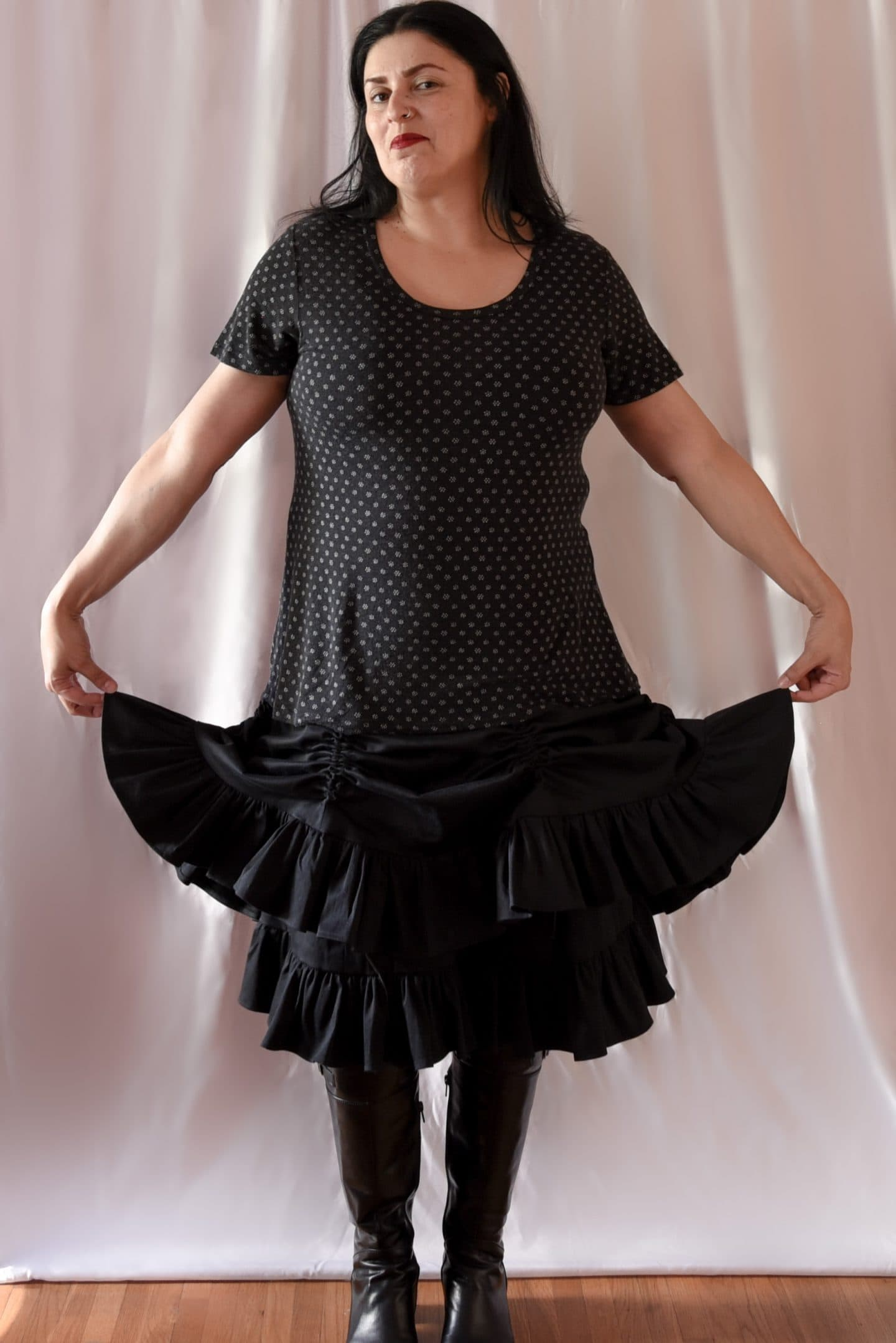 Image of a woman with long black hair smiling to the camera wearing a polka-dotted T-shirt and a Victorian-inspired black skirt with with two layers with the top skirt with two channels raised to created a bustle effect