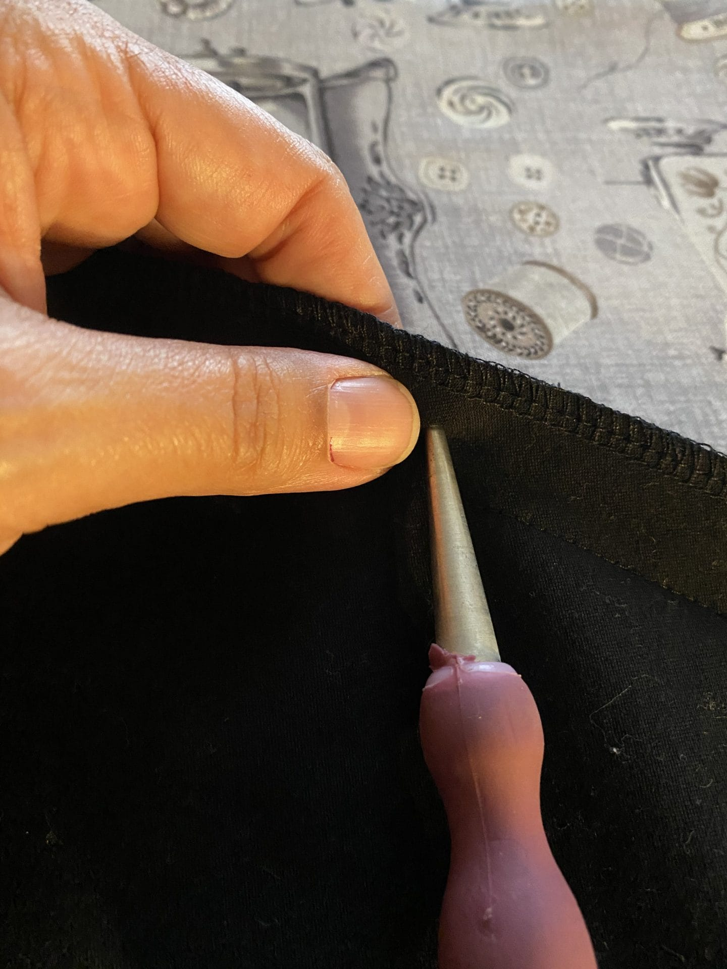 Image of awl piercing black fabric
