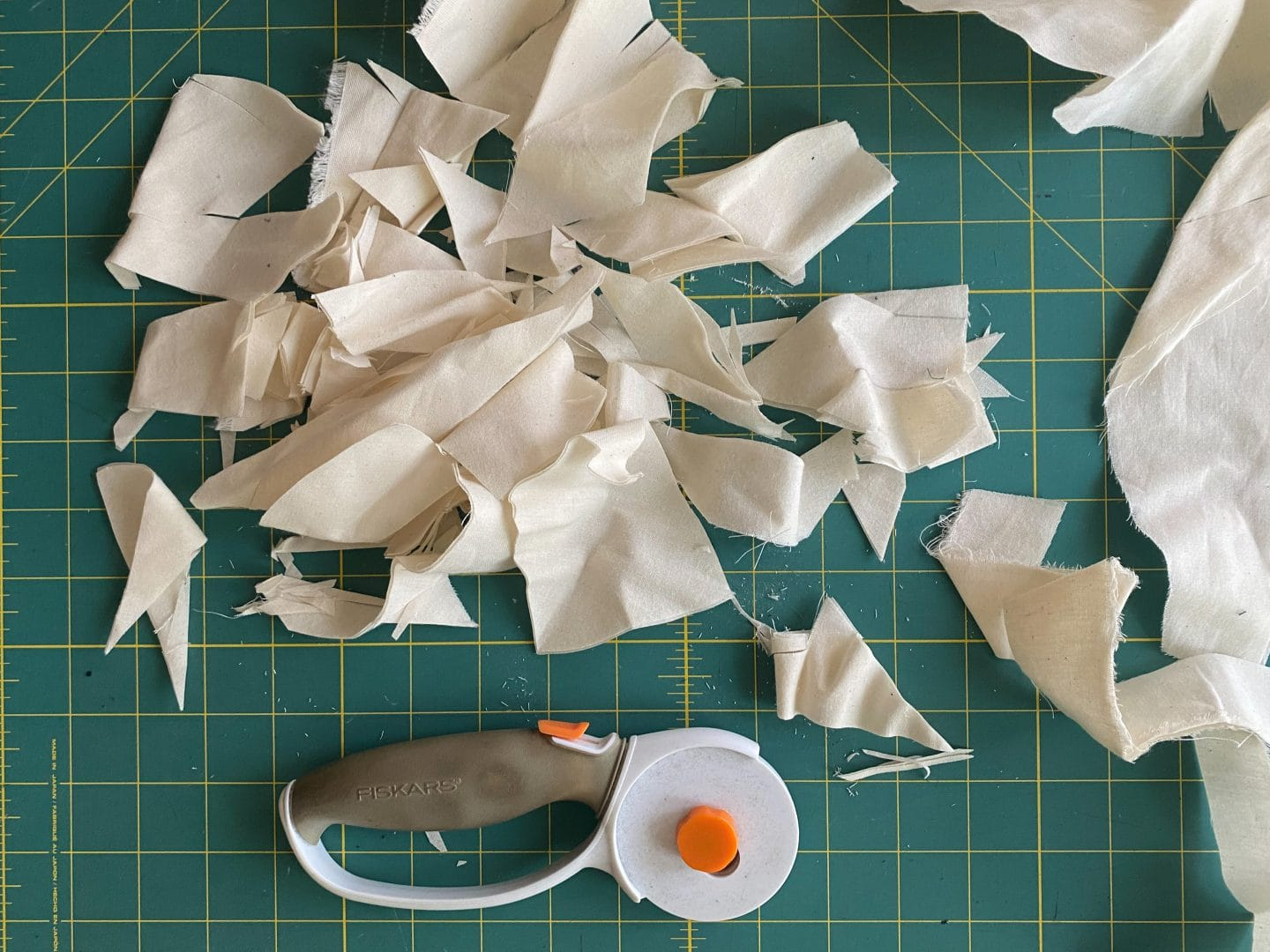 Image of scraps of muslin next to a rotary cutter on top of a green cutting mat