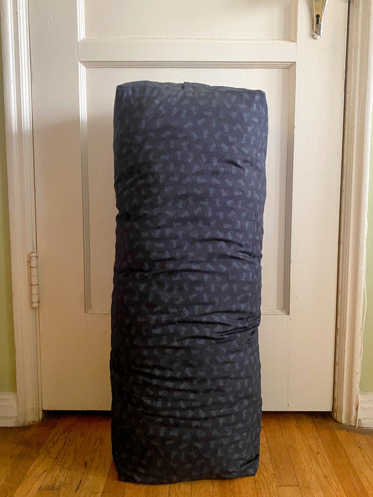 Image of a yoga bolster made with black fabric with dark gray kitty print propped against an old fashioned door.