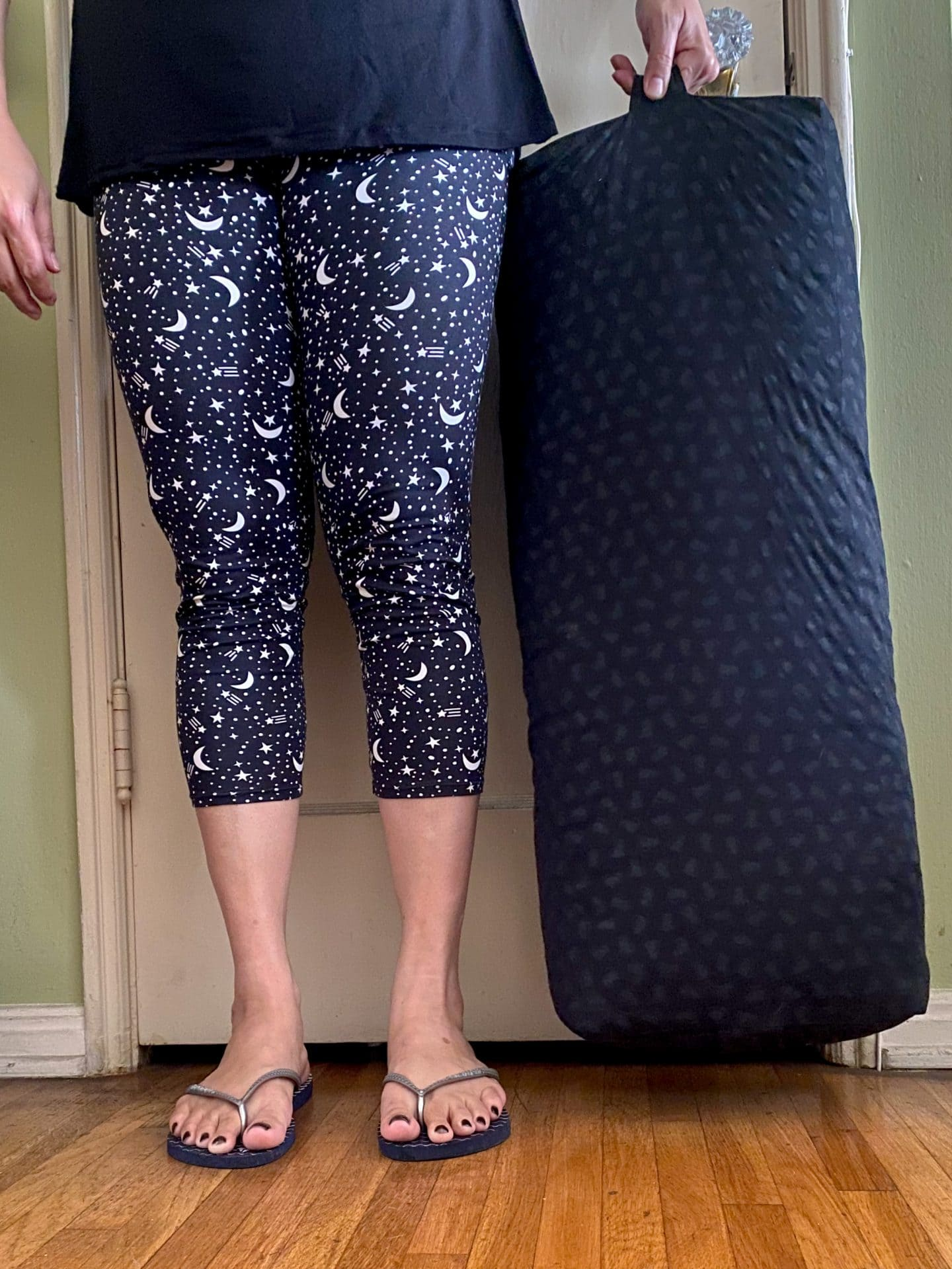Image of a woman's body from the waist down, the woman is wearing black leggings with white half moon and stars, silver flip flops, and holding a diy yoga bolster made of black cotton with dark gray cats from its handle as she stands in front of an old fashioned door