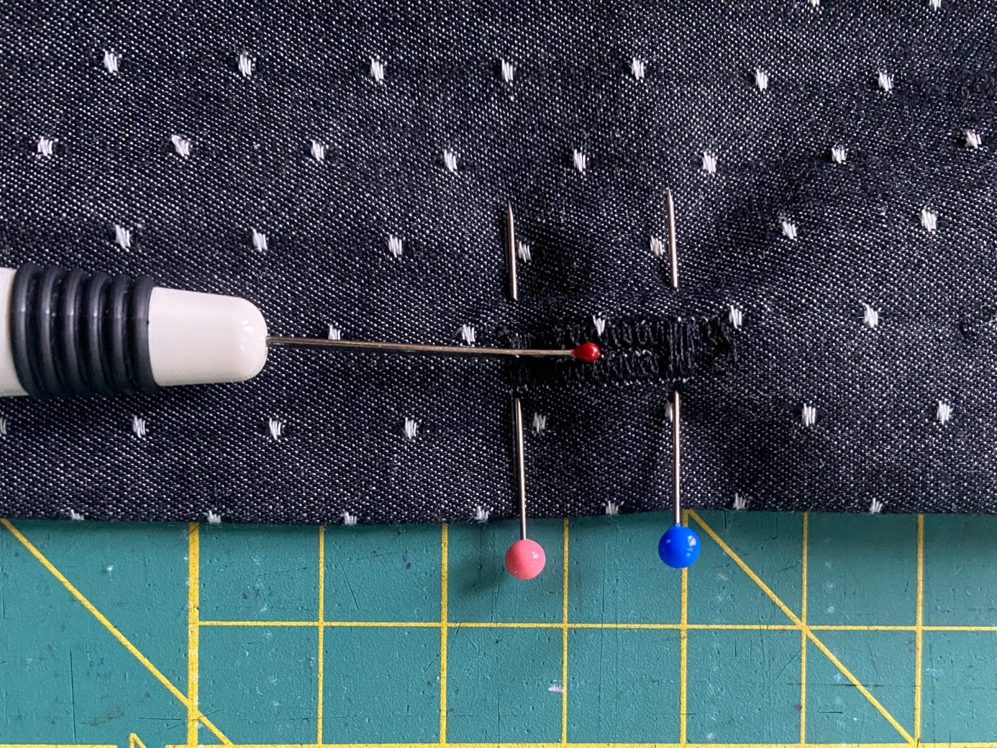 Image of a buttonhole with two pins marking the beginning and the end of the buttonhole and a seam ripper reading to cut the buttonhole open