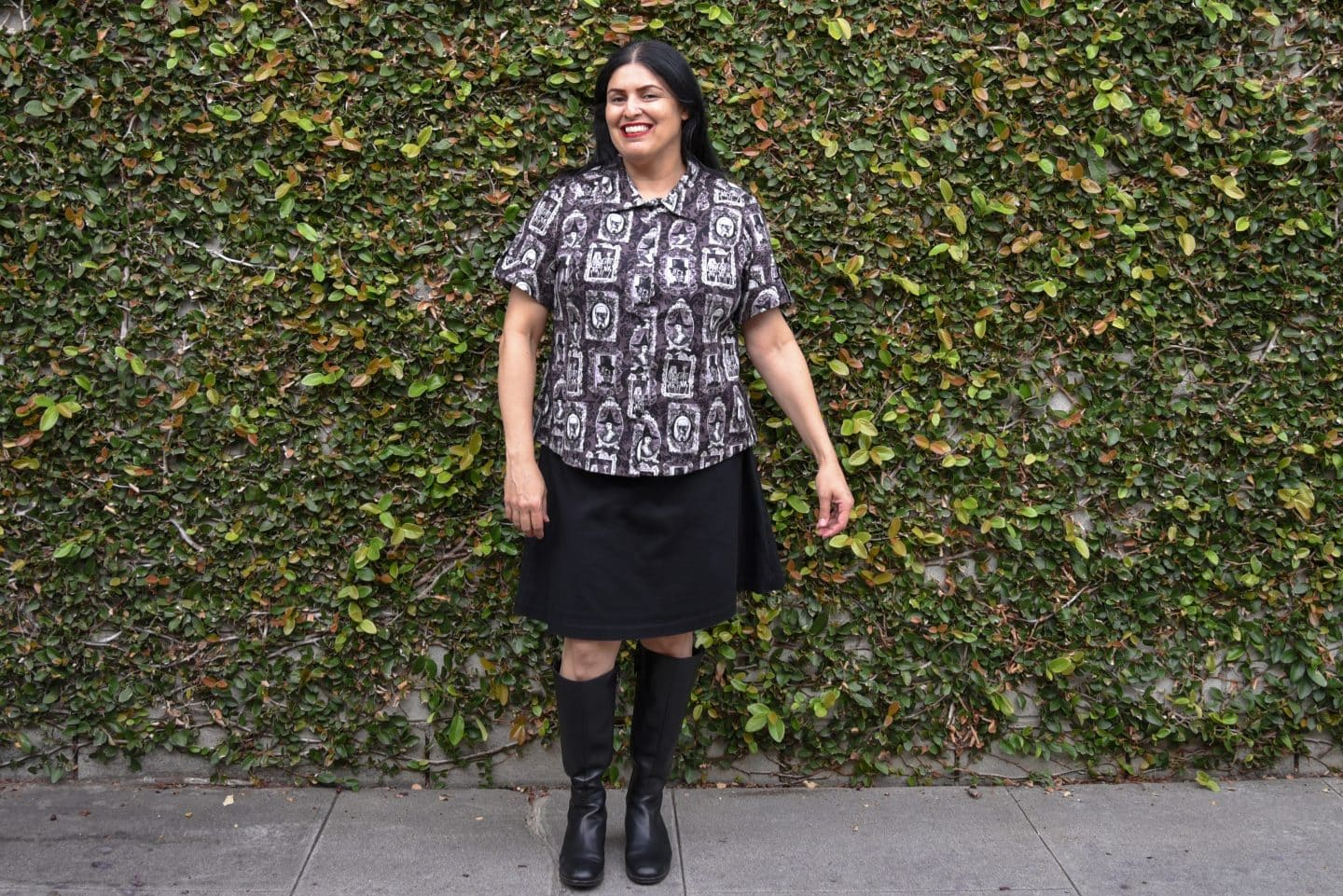 Image of a woman with long black hair standing in front of a wall covered in vine wearing a short-sleeved buttoned up shirt with a purple, black, and white print of skeletons in picture frames, black knee-length skirt, and black boots to her knees