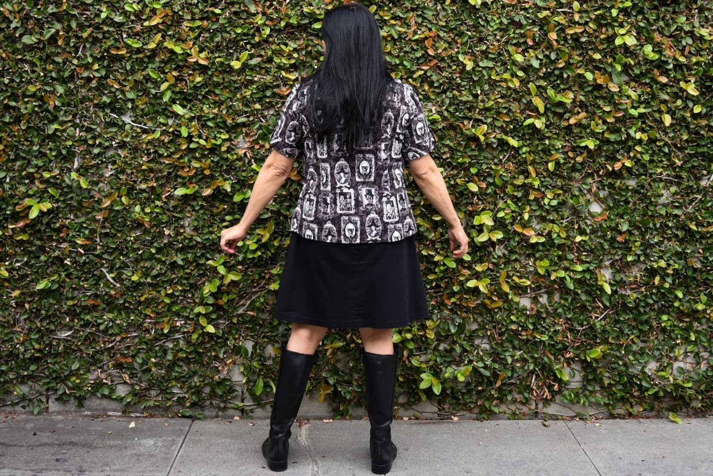 Image of a woman with long black hair standing with her back to the camera in front of a wall covered in vine wearing a short-sleeved buttoned up shirt with a purple, black, and white print of skeletons in picture frames, black knee-length skirt, and black boots to her knees