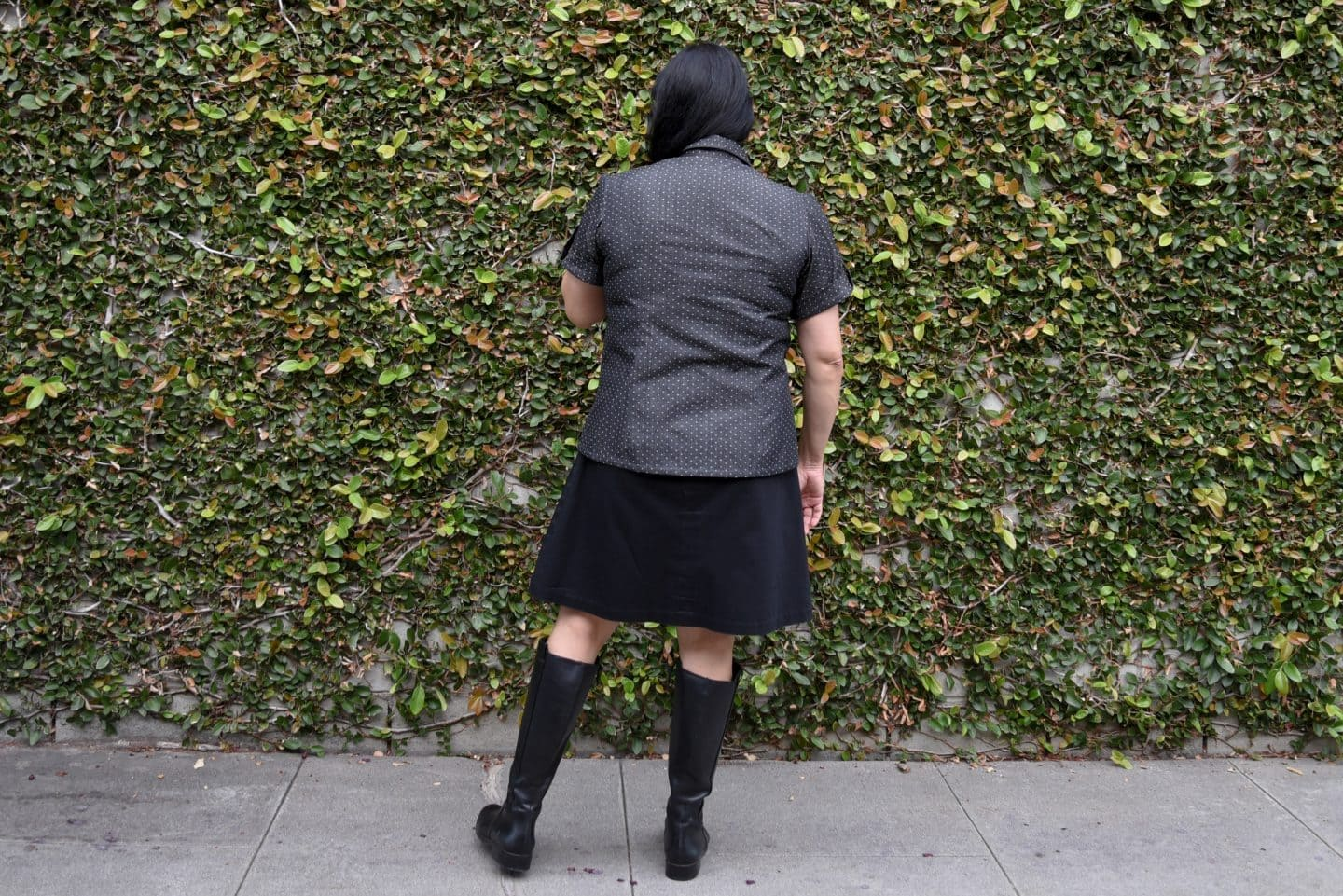 Image of a woman with long black hair standing with her back to the camera in front of a wall covered in vine wearing a short-sleeved polka-dotted buttoned up shirt, black knee-length skirt, and black boots to her knees