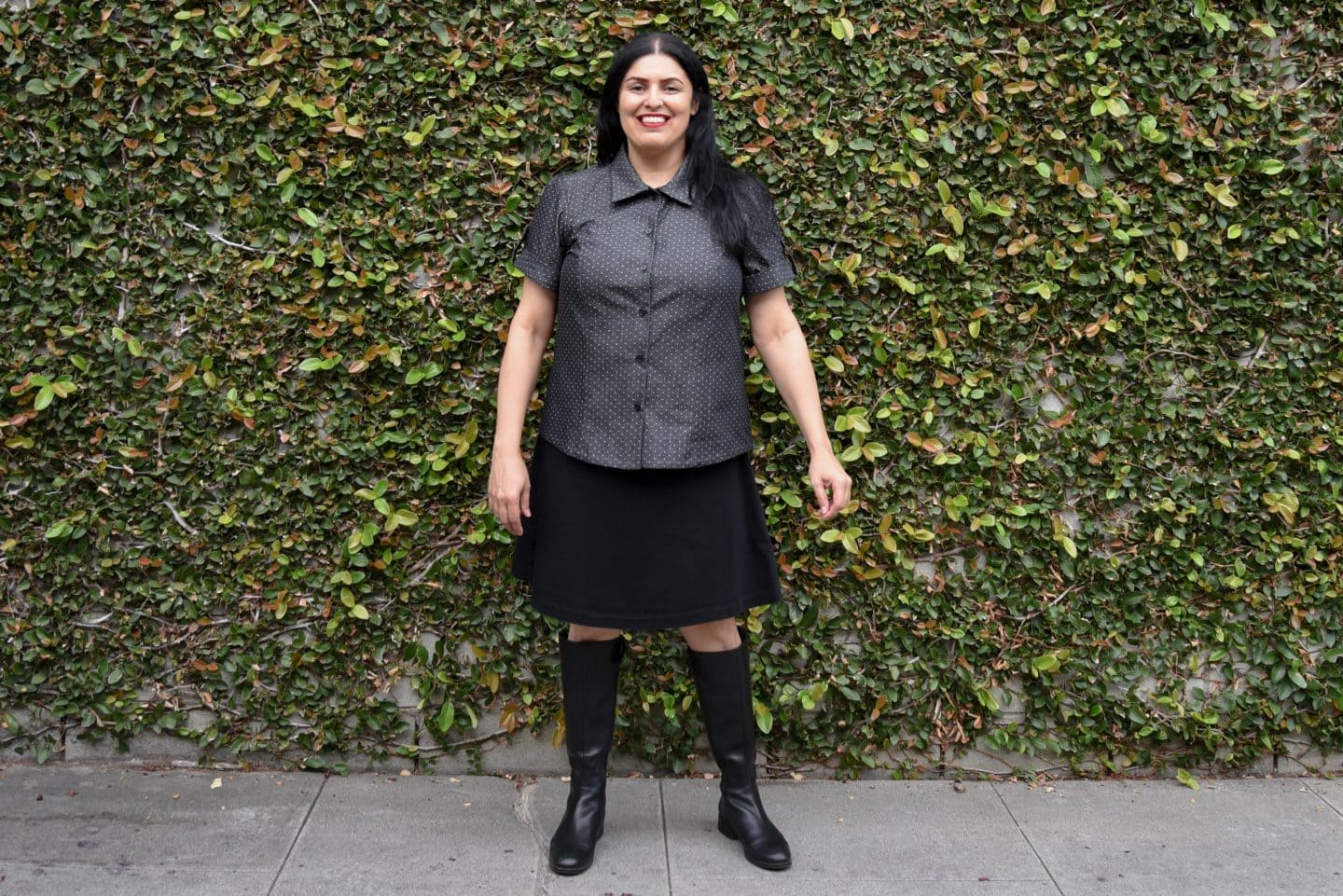 Image of a woman with long black hair standing in front of a wall covered in vine wearing a short-sleeved polka-dotted buttoned up shirt, black knee-length skirt, and black boots to her knees