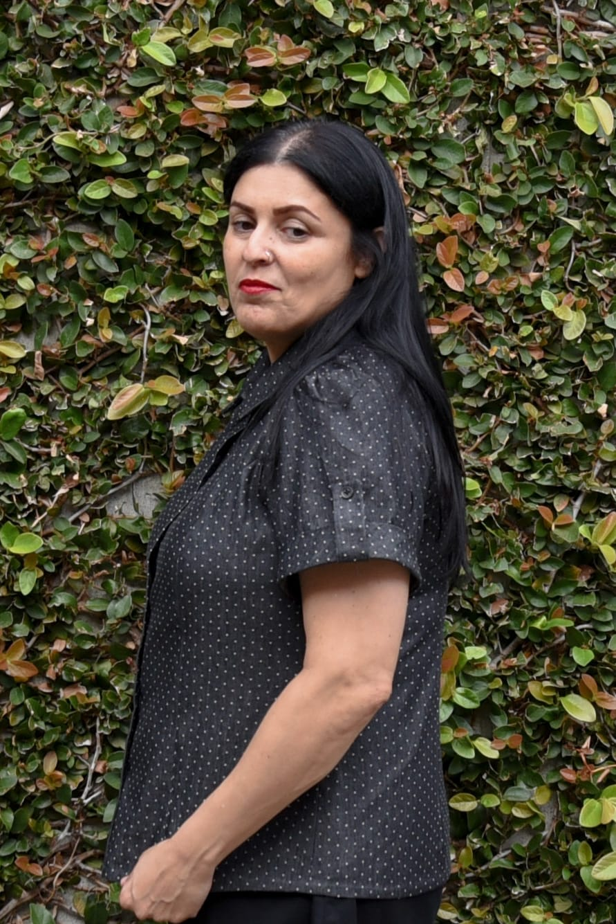 Image of a woman with long black hair standing sideways to the camera in front of a wall covered in vine wearing a short-sleeved polka-dotted buttoned up shirt, black knee-length skirt, and black boots to her knees