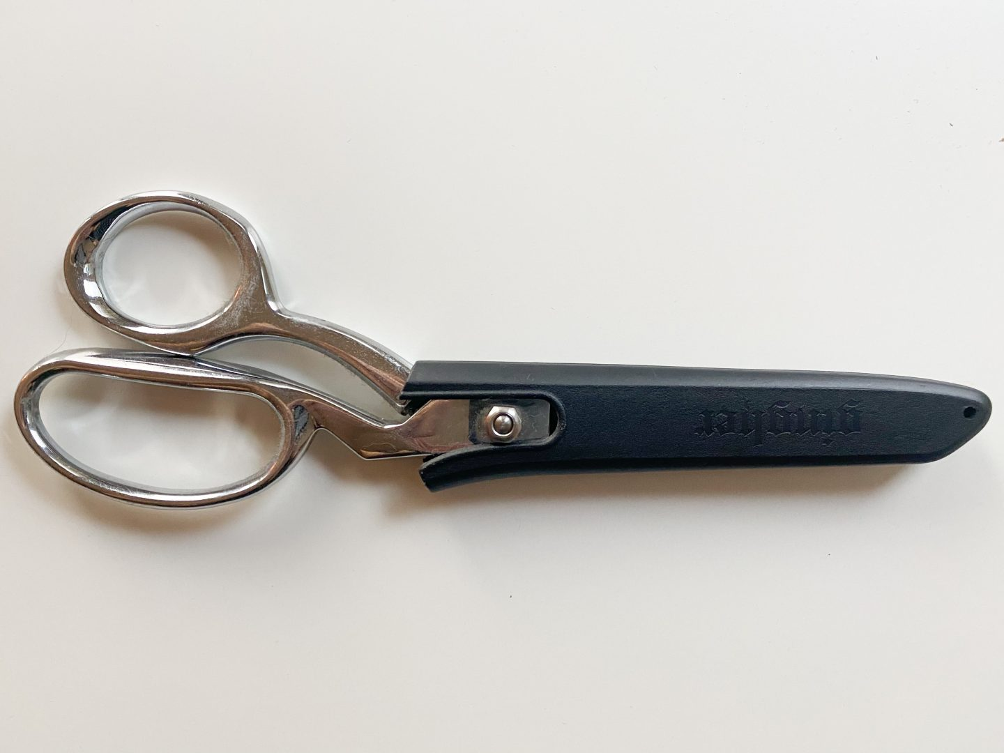Image of a pair of metal sewing shears in its protective black case against a white background.