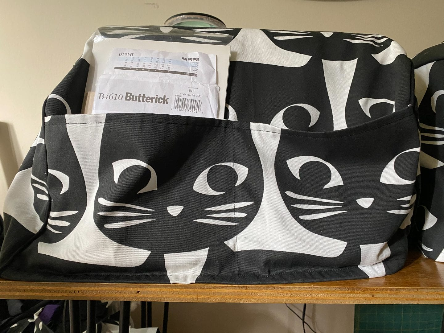 Image of a sewing machine on a table with a cover made of white canvas with big black cat faces as print
