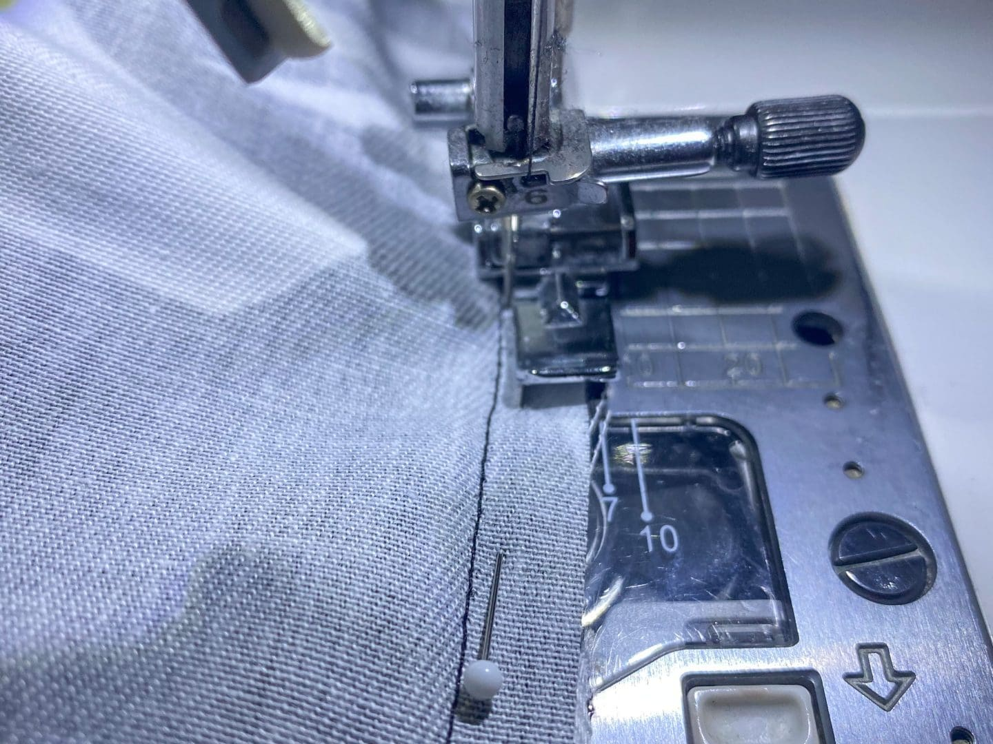 Image of sewing machine with zipper foot to sew piping