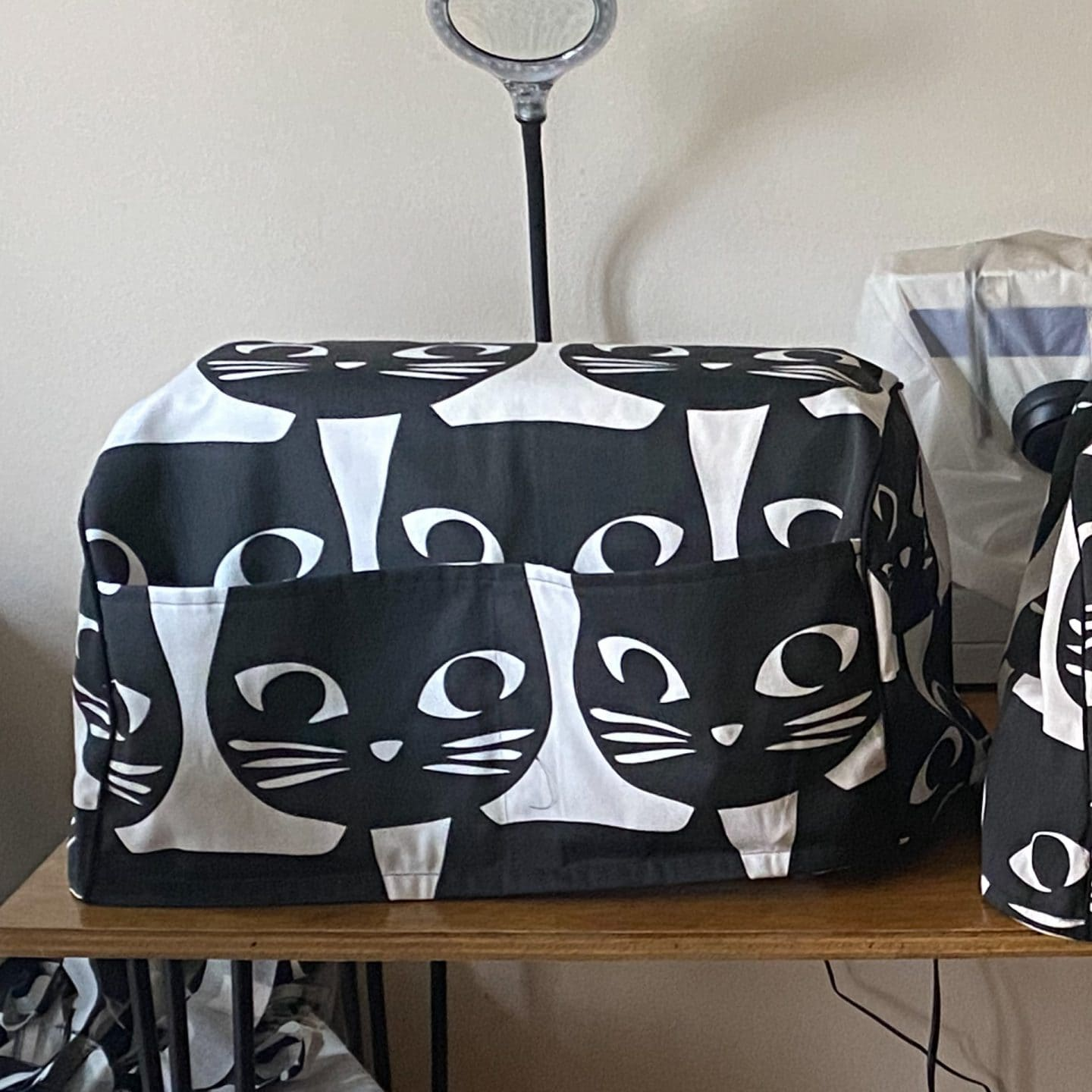 Image of a sewing machine with a cover made of canvas with big black cat print and black piping detail