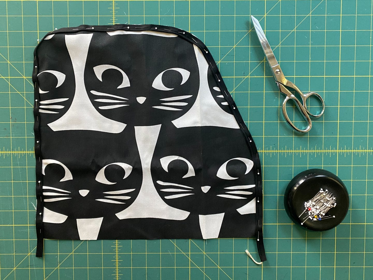 Image of side pattern piece for serger cover with piping pinned to it