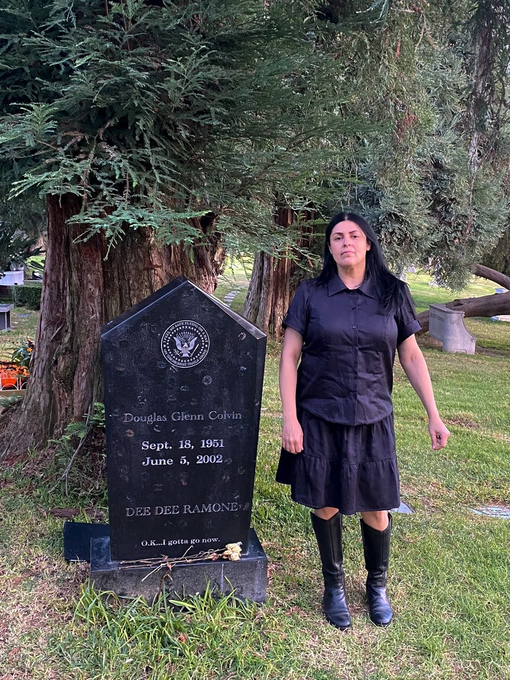 Image of a woman with long black hair standing next to a headstone wearing a buttoned up black shirt, a black skirt, and black boots