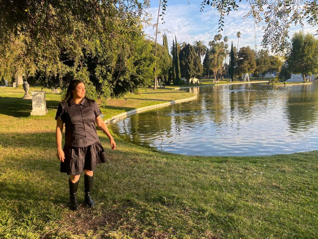 Image of a woman with long black hair standing in front of trees next to a small lake wearing a buttoned up black shirt, a black skirt, and black boots