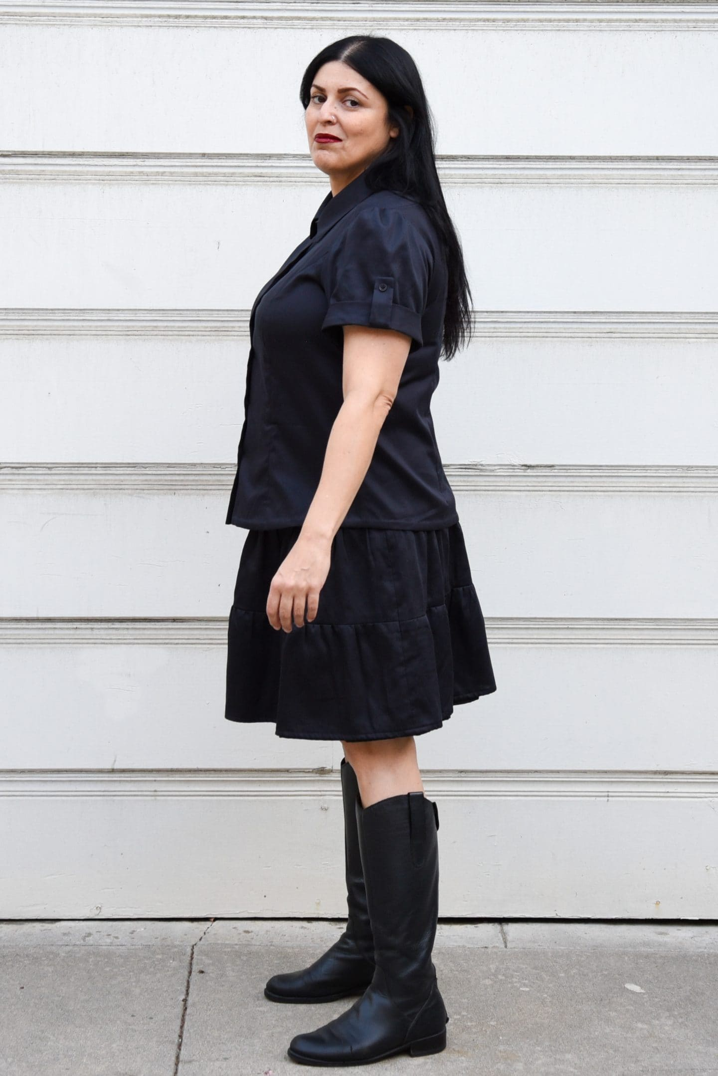 Image of a woman with long black hair standing in front of a white background wearing a buttoned up black shirt, a black skirt, and black boots