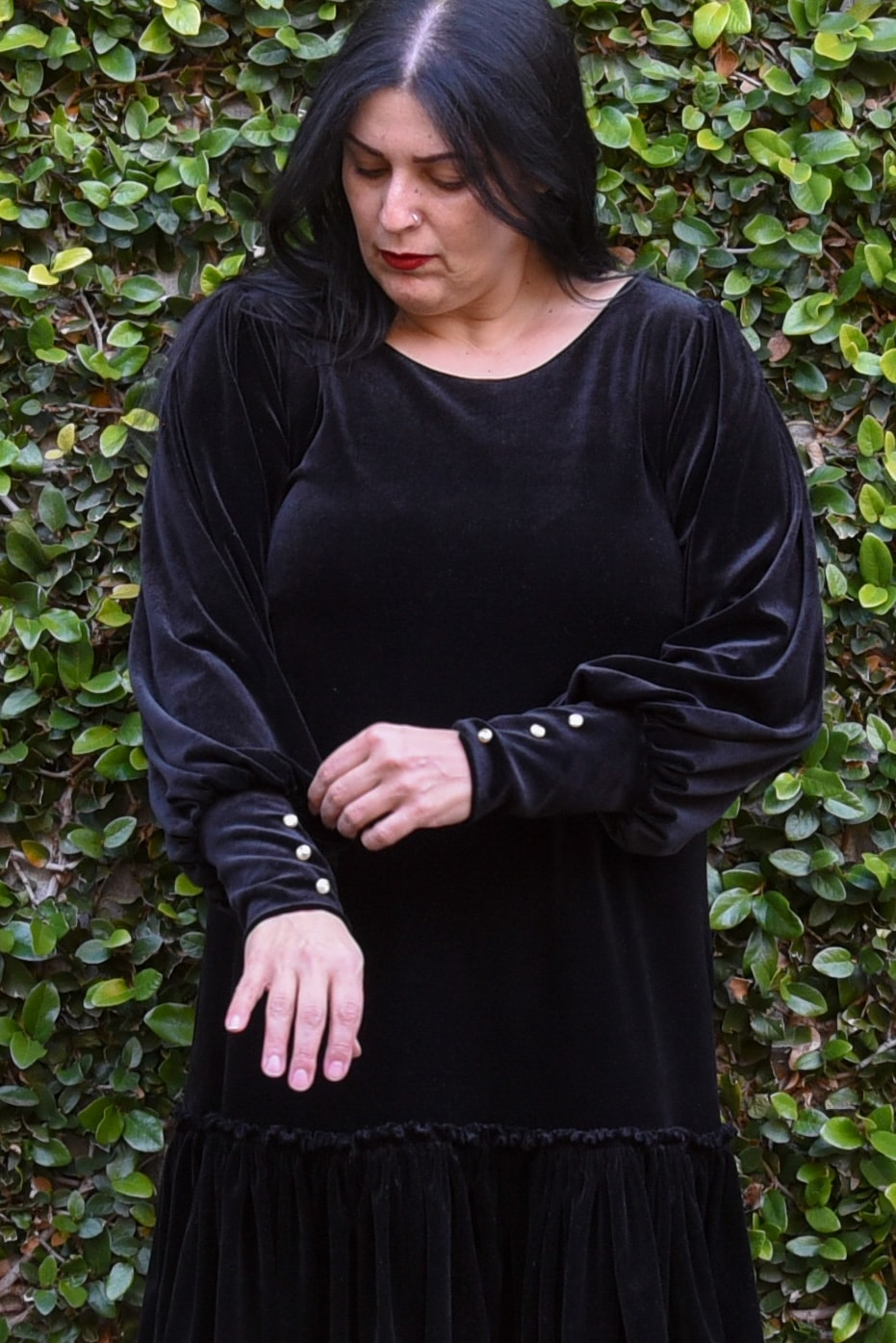 Image of a woman with long black hair and red lipstick wearing a black velvet dress with bishop sleeves and hem ruffles standing in front of a wall covered in vines.