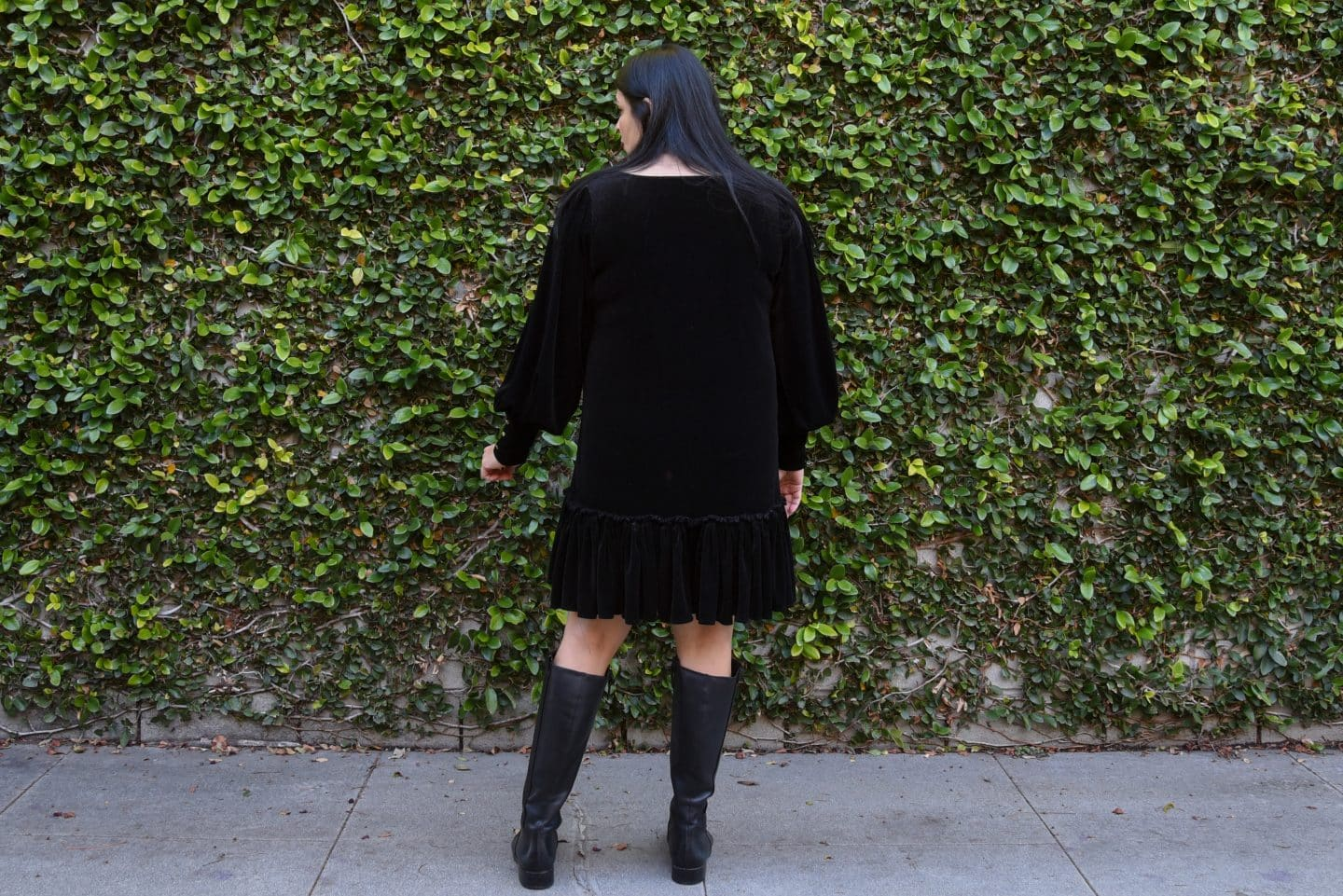 Image of a woman with long black hair with her back to the camera wearing a black velvet dress with bishop sleeves and hem ruffles standing in front of a wall covered in vines.