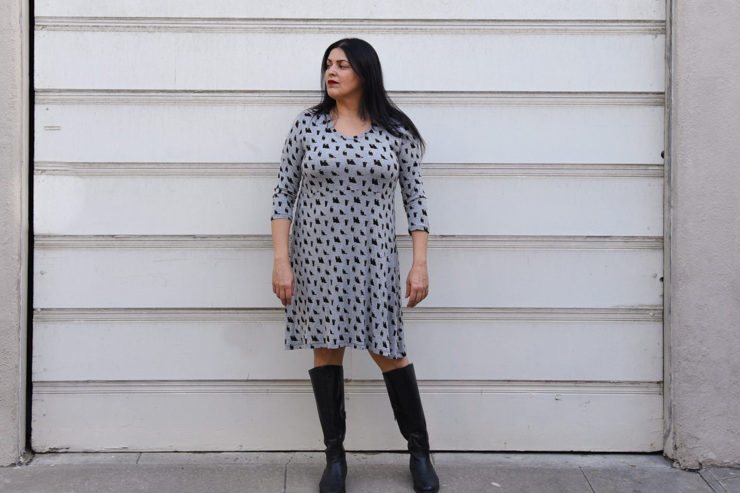 Image of a woman with long black hair and red lipstick facing the camera wearing a black and gray knit empire-waist dress with black kitty print standing in front of a white garage door.