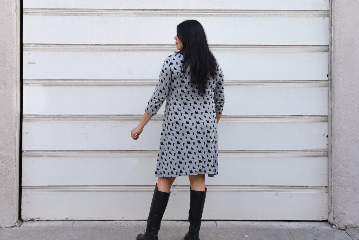 Image of a woman with long black hair and red lipstick with her back to the camera wearing a black and gray knit empire-waist dress with black kitty print standing in front of a white garage door.
