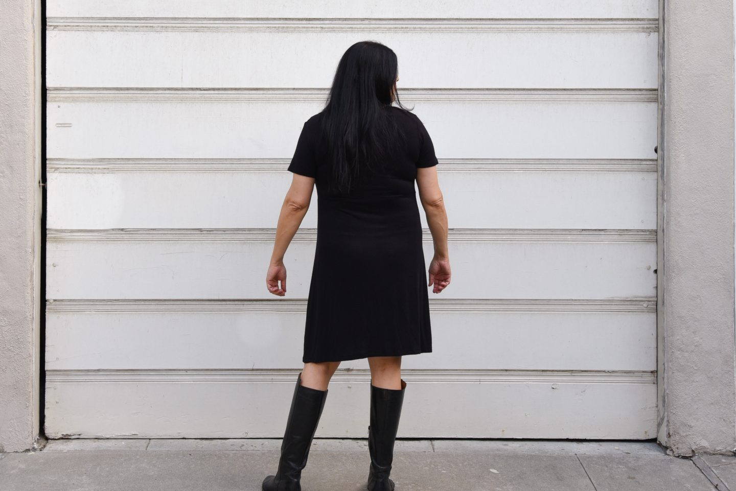 Image of a woman with her back to the camera with long black hair and red lipstick wearing a black knit empire-waist dress with black kitty print standing in front of a white garage door.