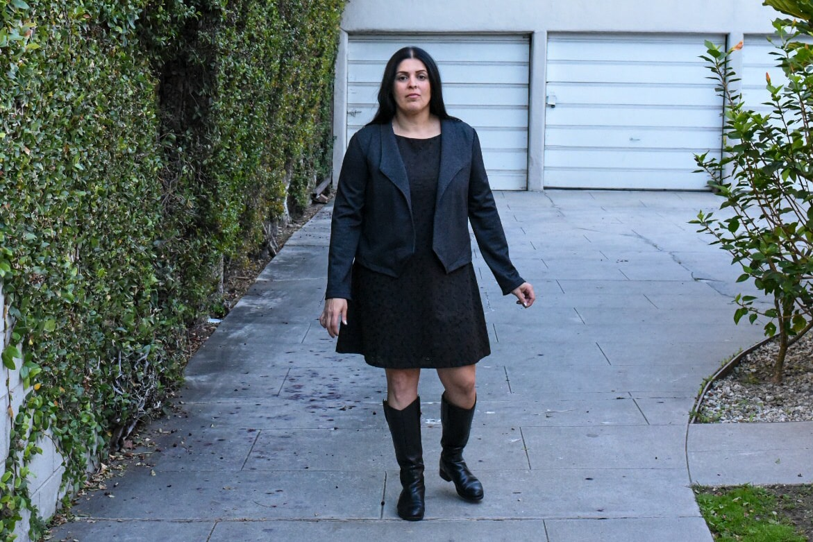 Image of a woman with black long hair wearing a cropped tweed jacket, a mini black dress, and boots standing in front of garage doors