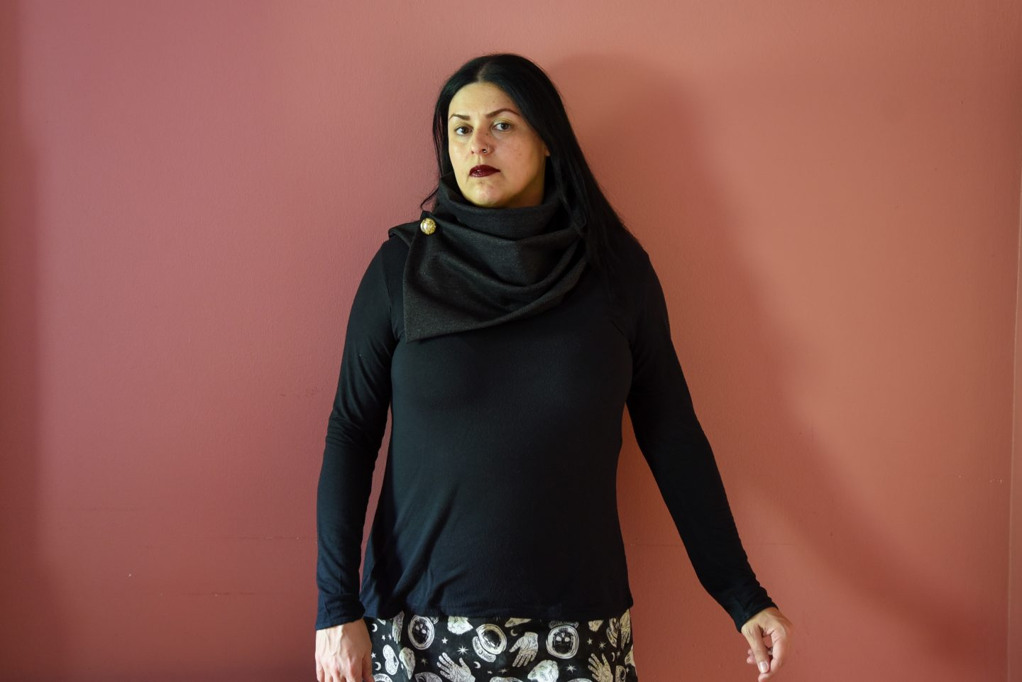 Image of a woman with long black hair and red lipstick wearing a dark gray cowl and black top standing in front of a pink wall