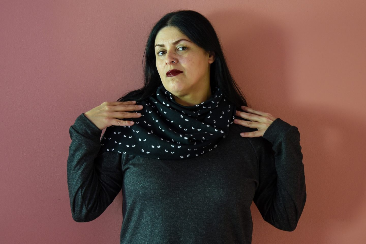 Image of a woman with long black hair and red lipstick wearing a black fabric cowl with glow-in-the-dark eye print and gray top standing in front of a pink wall