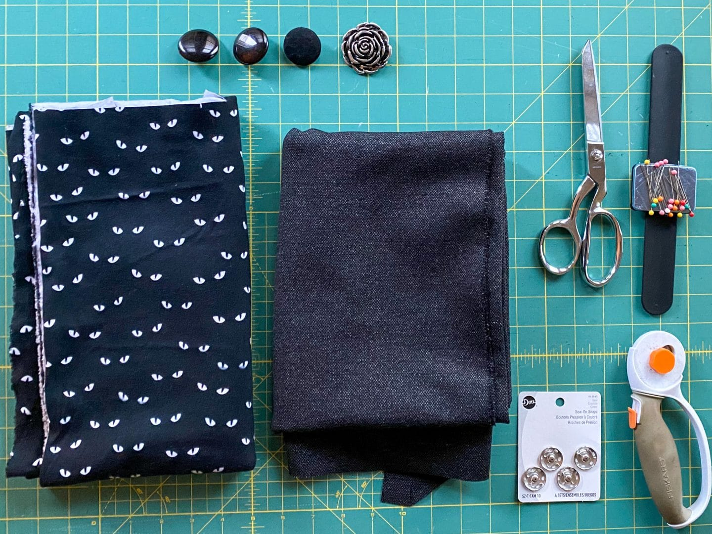 Image of two pieces of fabric, one black interlock fabric with glow-in-the-dark eyes, one piece of ponte de roma tweed, buttons, scissors, pins, snaps, and rotary cutter on a green cutting mat