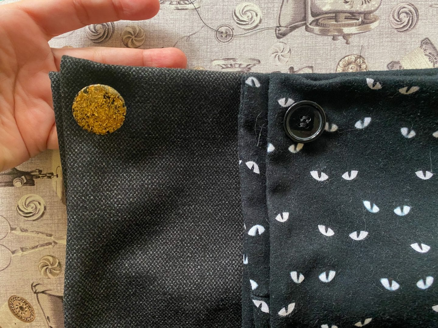 Detail image of both cowls, the tweed one with a golden button, and the glow-in-the-dark one with a black button