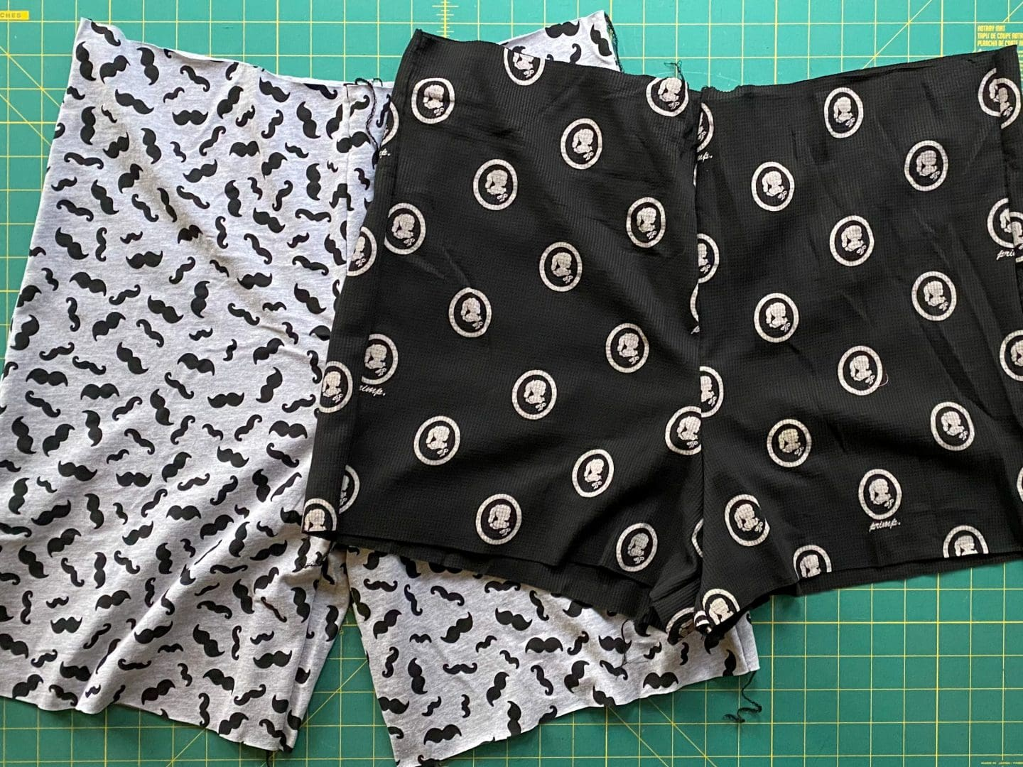 Image of two pairs of shorts, one gray with black mustaches, one black with white cameos, waistband and hems unfinished, on a green cutting board