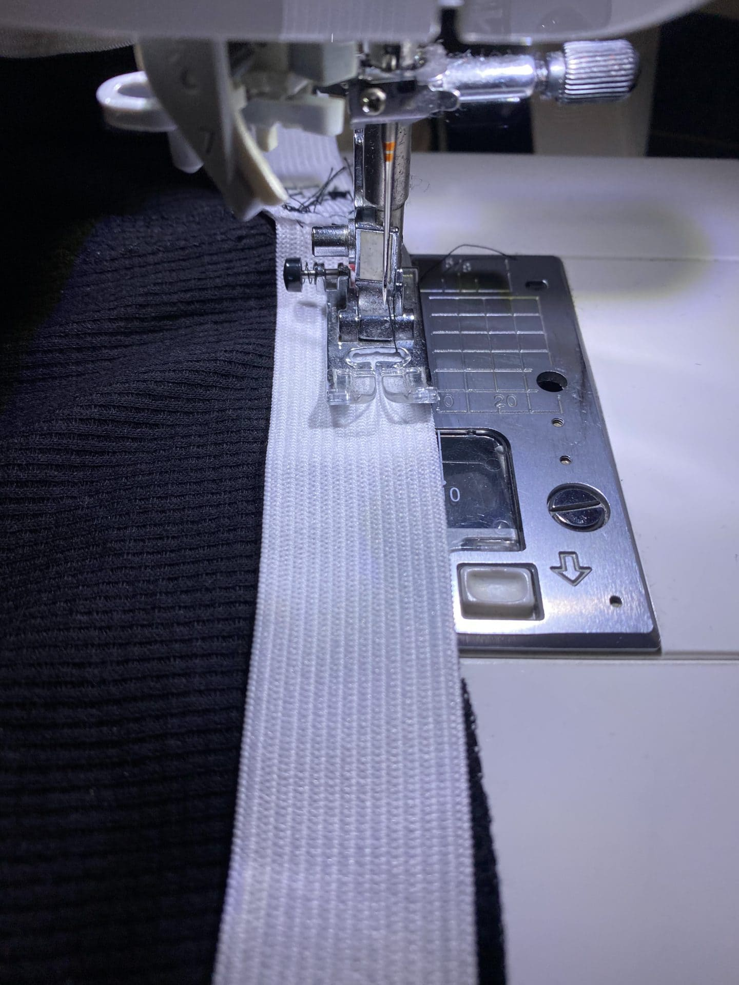 Detail image of a sewing machine with a piece of elastic being sewn to the edge of a black piece of fabric