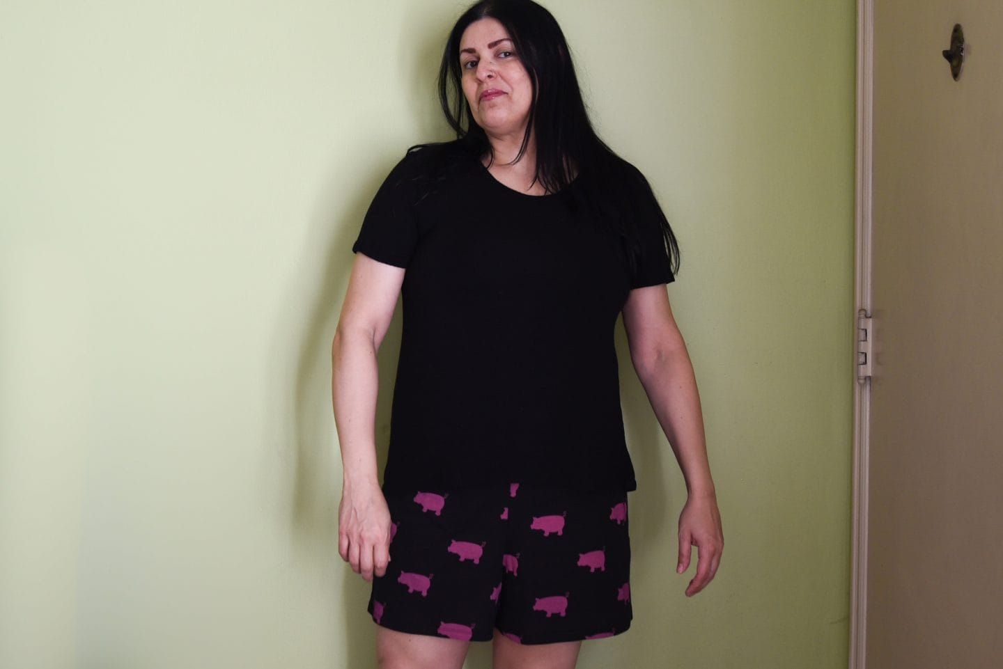 Image of a woman with long black hair standing in front of a green wall wearing a black T-shirt and black shorts with pink pigs