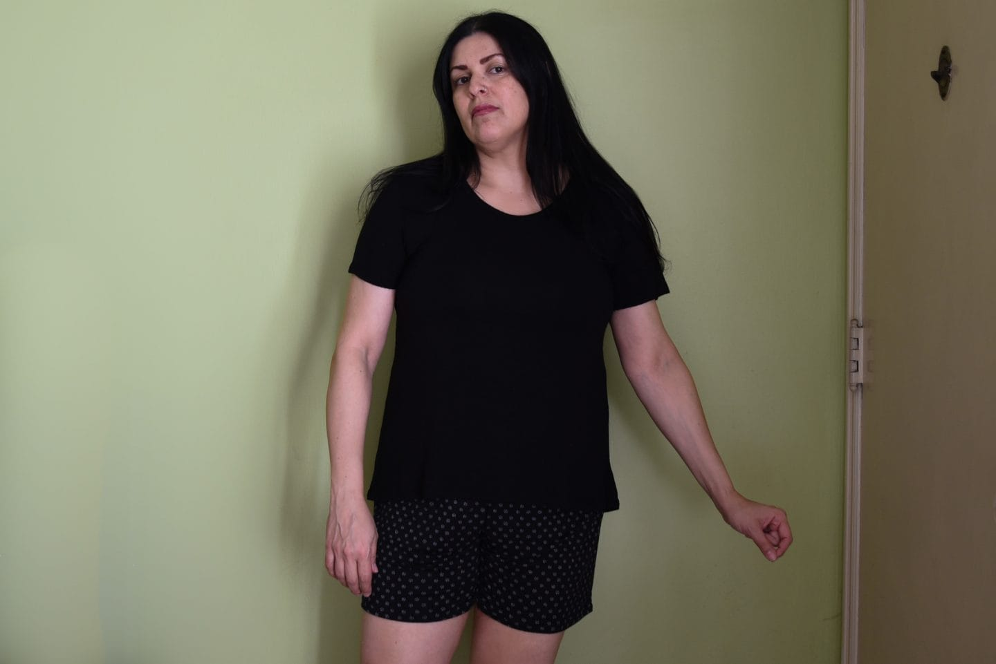 Image of a woman with long black hair standing in front of a green wall wearing a black T-shirt and black shorts with white polka dots