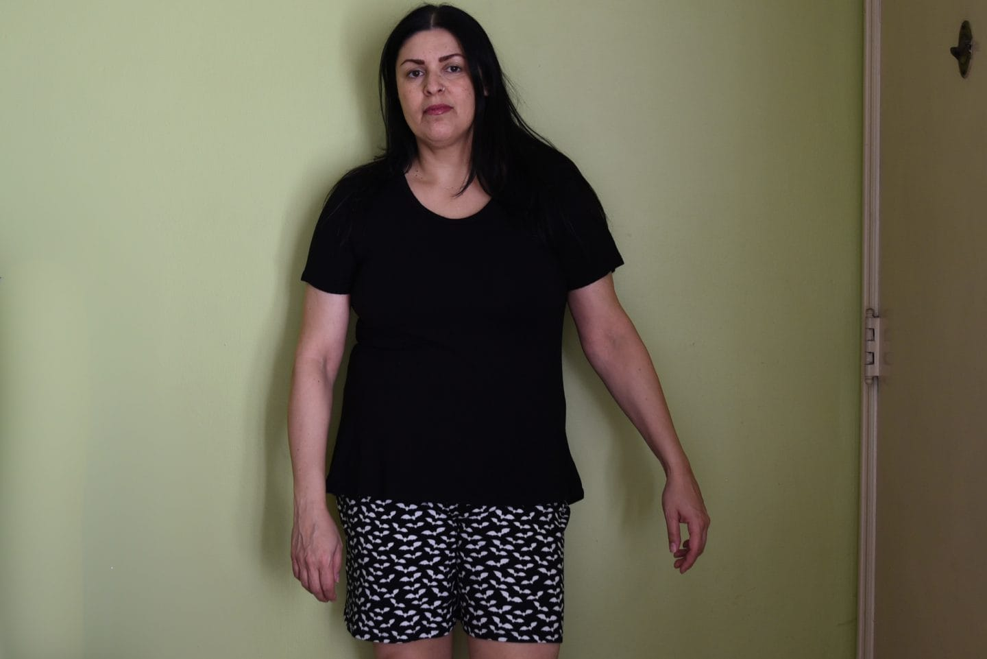 Image of a woman with long black hair standing in front of a green wall wearing a black T-shirt and black shorts with white bats
