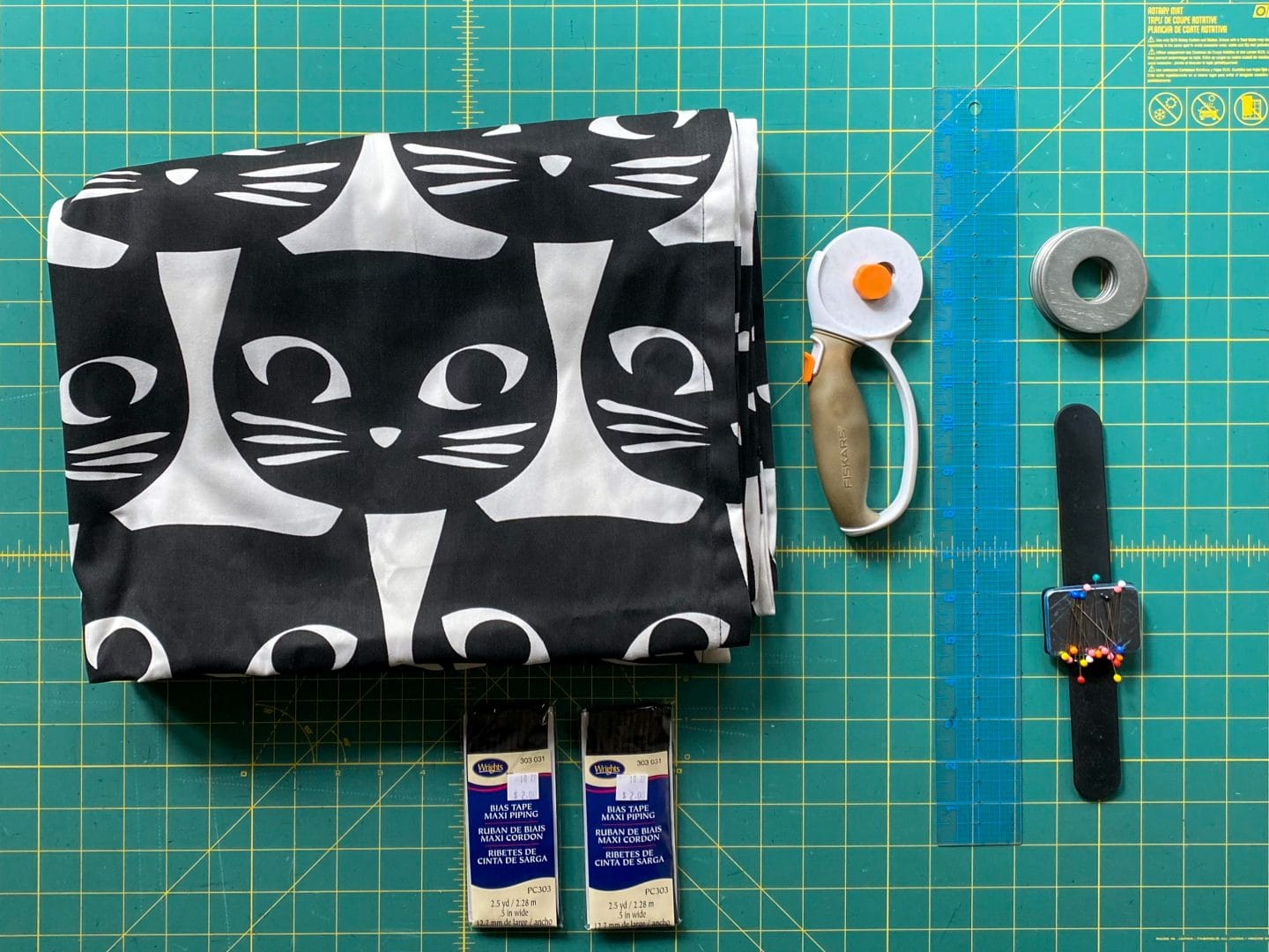 Image of all the supplies to you will need to sew your pillows: White canvas fabric with large black cat faces, rotary cutter, ruler, fabric weights, pins, and piping.