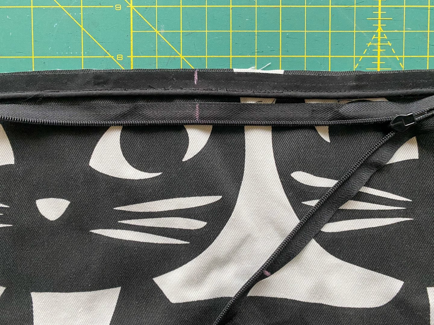 Image of one side of the pillow with a mark to identify the middle of the side and a black zipper with a mark to identify the middle of the zipper