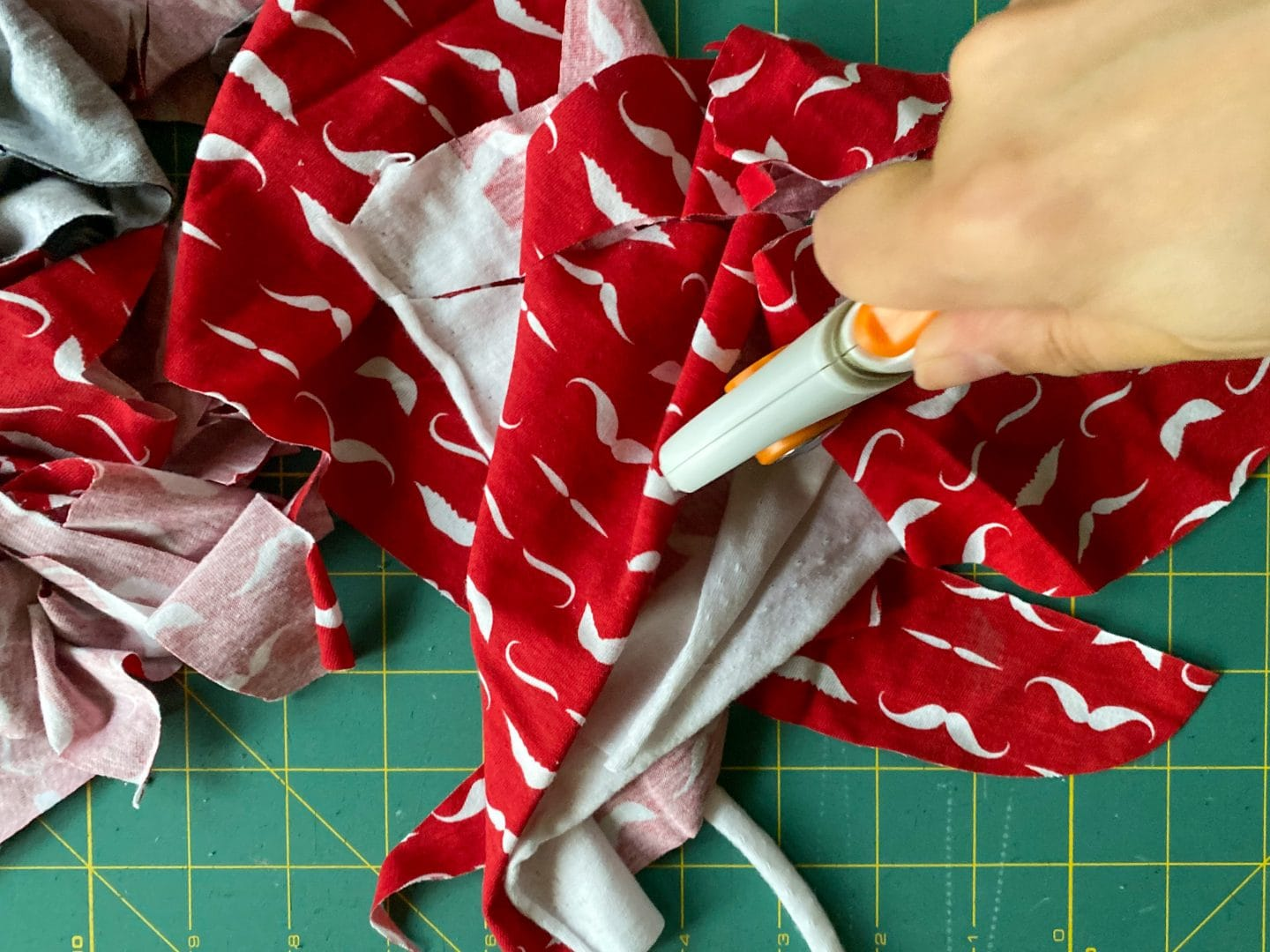 Image of fabric scraps being shredded with a rotary cutter