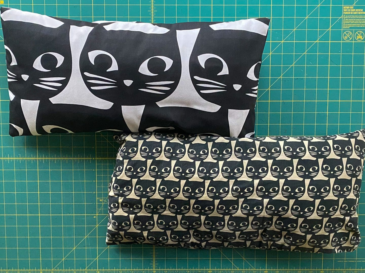 Image of two pillows, one with big black cat faces on white canvas and the other with small black cat faces on cotton fabric
