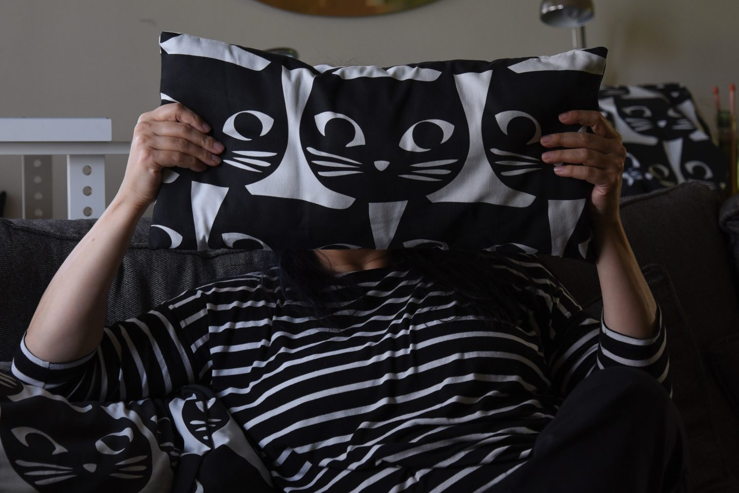 Image of a woman wearing black and white striped shirt holding a black and white cat pillow in front of her face