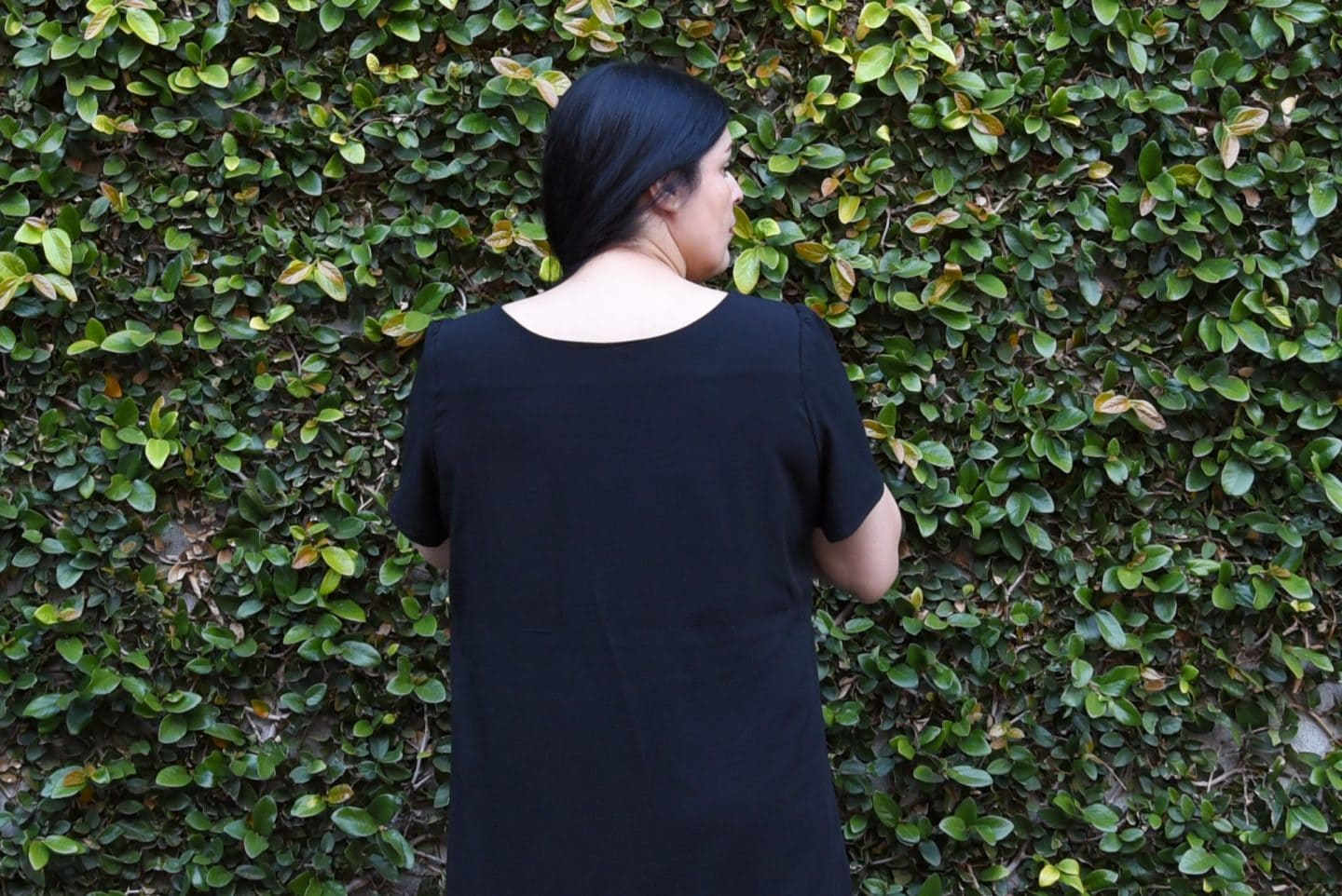 Detail image of woman with long black hair with her back to the camera facing a wall covered in wines wearing a black rayon dress with nice, flat facing
