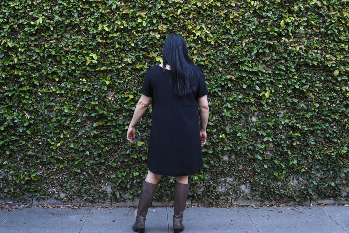 Image of woman with long black hair with her back to the camera facing a wall covered in wines wearing a black rayon dress and gray boots