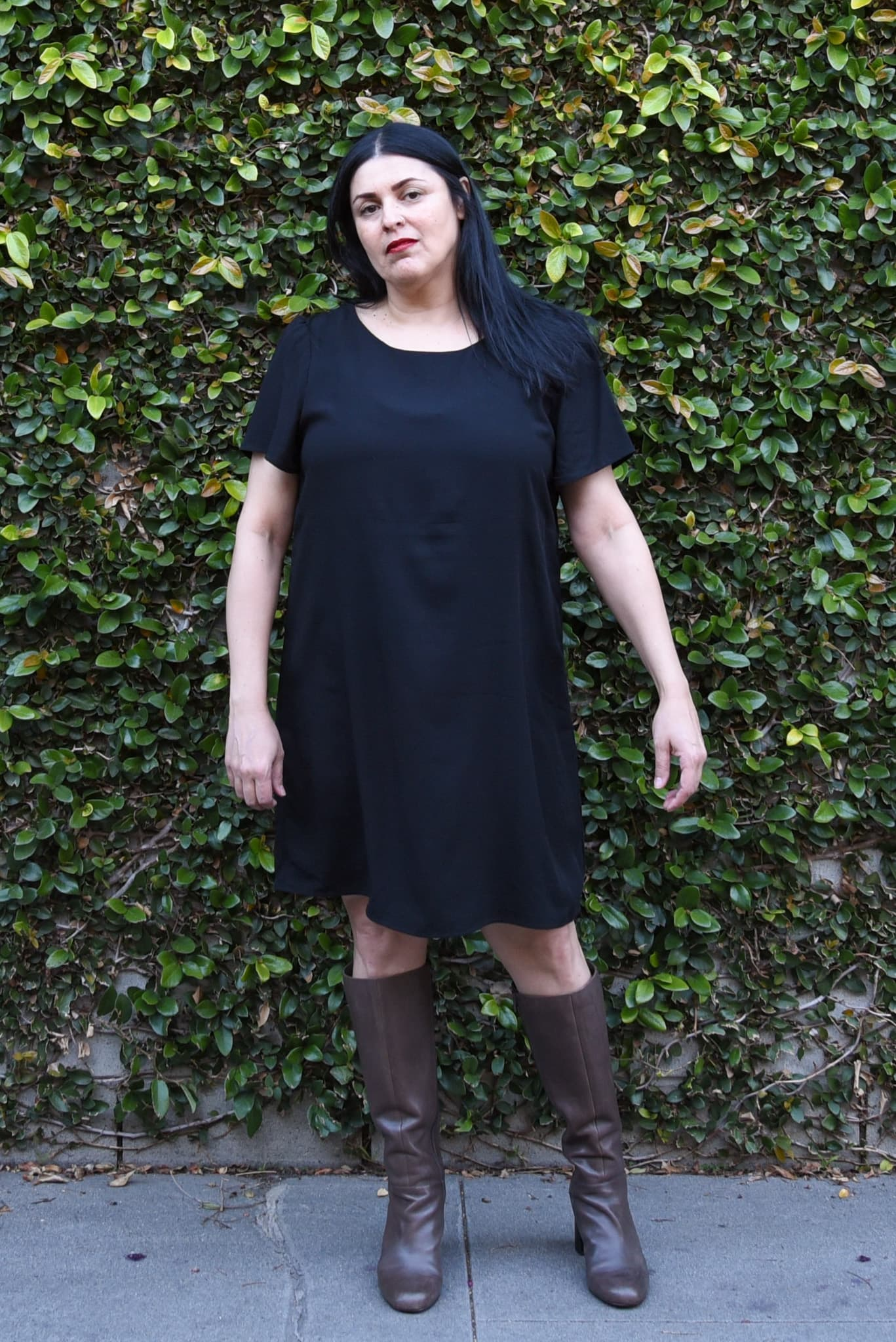 Image of woman with long black hair and red lipstick standing in front of a wall covered in wines wearing a black rayon dress and gray boots